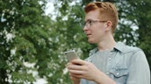 Handsome male student in glasses is using smartphone in park outdoors smiling enjoying device touching screen. People and modern gadgets concept.