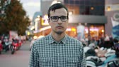 Slow motion of serious young businessman in glasses standing alone in city street and looking at camera. Emotions, youth and summer evening concept. Vídeos
