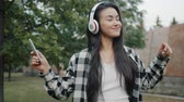 Good-looking Asian student in casual clothing is enjoying music in headphones dancing outdoors having fun alone holding smartphone. People, lifestyle and youth concept.