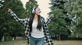 Happy Asian student dancing outdoors wearing wireless headphones smiling enjoying music and leisure time in city park. Youth and entertainment concept.