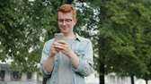 Cheerful person handsome redhead guy is touching smartphone screen outdoors in city park standing alone using gadget. People, lifestyle and devices concept.