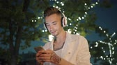 Slow motion of young man listening to music outdoors with smartphone and headphones having fun enjoying leisure time alone. People and devices concept.