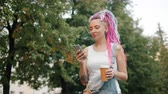 Cute girl punk with colorful hair is walking outdoors in park with smartphone and take out coffee smiling enjoying leisure time. People and lifestyle concept. Vídeos