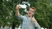 Joyful young man is taking selfie with smartphone camera outdoors showing thumbs-up and v-sign hand gestures posing and smiling in park. Youth and photograph concept.