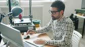 Handsome guy in glasses is working with computer while modern 3d printer is modeling plastic shape in background. People, work and innovation concept.