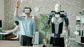 ar : Smart robot is moving arm like young woman in virtual reality glasses in office, people are working in background. Robotic engineering and modern business concept. Stock Footage