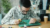 microprocesador : Microelectronics engineer handsome bearded guy in glasses is repairing microcircuit board for robot working in office. People and profession concept.