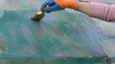 ferrugem : Worker applying rust converter to old metal plate, closeup of hand and brush tool