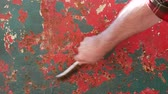 ferrugem : Rust removing from old metal roof plate using wire brush, closeup of hand with tool
