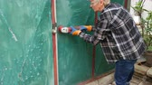 ferrugem : Female worker removing paint and rust from old metal door plate using wire brush at grinder power tool Vídeos