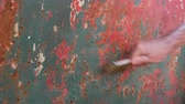 weathered : Rust removing from metal using wire brush, closeup oh worker hand with tool