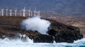the strength of the waves against the rocks and wind turbines