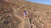 girl climbs up to the slope of a mountain Wideo