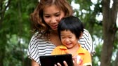 An Asian boy and mother are playing funny game on tablet.
