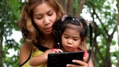 An asian girl and mother are playing funny game on tablet at the park Стоковые видеозаписи