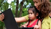 An asian girl and mother are using notebook computer at the park Стоковые видеозаписи