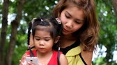 An asian girl and mother are playing funny game on smart phone at the park Стоковые видеозаписи