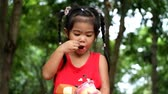 An asian girl enjoys eating delicious cupcake at the park.