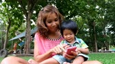 An asian boy and mother are playing funny game on smart phone at the park Стоковые видеозаписи
