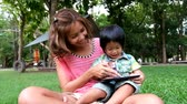 An asian boy and mother are playing funny game on tablet at the park