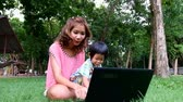 An asian boy and mother are using notebook computer at the park