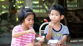 two asian kids boy and girl eat ice cream Стоковые видеозаписи