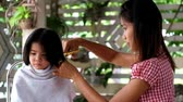 Mother hair dresses  her girl, mom hair dresses her kid daughter. girl annoy mother cut her hair
