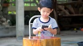 Asian boy playing games on smart phone joyfully, asian boy celebration on winning game on   smartphone.