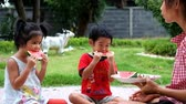 Mother Daughter and son Enjoying Slices Of Water Melon, mother son and daughter enjoy eating   water melon