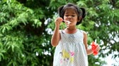 Cute little girl is blowing a soap bubbles, cute asian girl playing soap bubbles