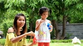 mother and daughter are blowing a soap bubbles, cute asian girl and mother playing soap bubbles