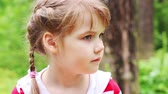 životní styl : Little cute serious girl looks around in summer park. Close up view