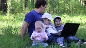 brother : Father with three children sit on grass with laptop in forest