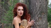 snarling : Pretty young woman poses as animal near tree in autumn forest at sunny day