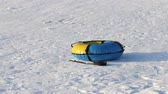 tobogganing : Yellow and blue snowtube is on white snow at winter sunny day
