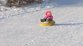 tobogganing : Little girl slides on a snowtube down from a hill at sunny winter day Stock Footage