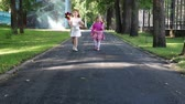 millsime : Two happy little girls walking with windmills in green summer park Stock Footage