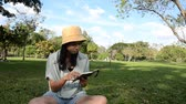 Young woman with yellow hat reading book in the park