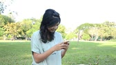 Young woman typing e-mail message on smartphone and laughing 影像素材