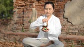 Woman playing a tibetan bowl,  traditionally used to aid meditation in Buddhist cultures.