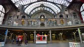 clock : Antwerp Belgium  May 11 2015: People in hall of Antwerp Central station on May 11 2015 in Antwerp Belgium. The station is widely regarded as the finest example of railway architecture in Belgium.
