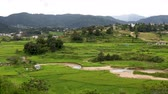 Green farm land with river flowing in the middle in hilly region Стоковые видеозаписи