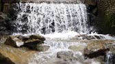 Small waterfall on a sunny day. Selective focus, focus on stone.