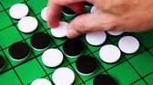 szachy : people are playing reversi, board game. this game suitable for adult, kids for practice planning intelligent strategy. its 4k time lapse footage.