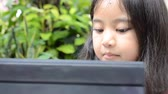 pretty : Little Asian girl playing tablet on the table Stock Footage