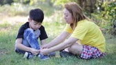 springseil : Asian cute Kind mit Mutter bindet Schnürsenkel im Park. Stock Footage