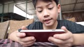 brother : Asian child using a digital tablet together .