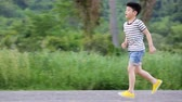 brother : Asian Kids Run on the road. Asian child playing outdoors. pan camera