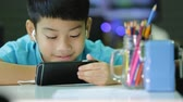 Asian child using a digital tablet with ear buds on his smart phone. Dostupné videozáznamy