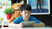 comunicação : 4k, Young asian boy browsing the internet on a digital tablet at home.